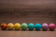 Easter eggs row on wooden background Royalty Free Stock Photos