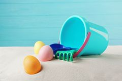 Easter eggs with sand and pail. On wooden blue background royalty free stock image