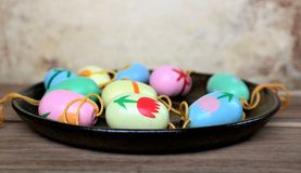 Easter eggs on a saucer, colorful scene. Decoration for Easter branches Stock Image