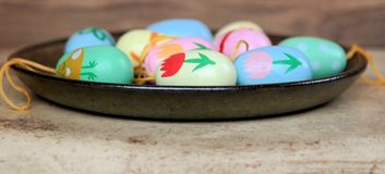 Easter eggs on a saucer, decoration for Easter branches. Easter eggs on a saucer, colorful scene, decoration for Easter branches Stock Image