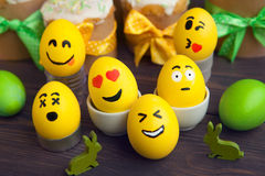 Easter eggs with smiley faces. On wooden background Royalty Free Stock Images