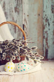 Easter eggs with spring branches of a willow in a basket . Stock Photo