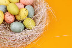 Easter Eggs in Straw. Speckled Colored Easter Eggs with straw on orange background. Copy Space royalty free stock photo