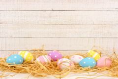 Easter Eggs in straw against white wood. Easter Eggs in straw against an aged white wood background Stock Images
