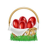 Easter eggs in straw basket on grass isolated Stock Photo