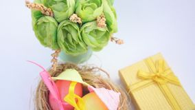 Easter eggs in straw nest and spring flowers stock video