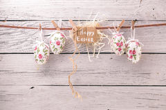 Easter eggs on a string. With flowers on a light wooden background with a congratulatory card ,concept holidays Royalty Free Stock Images