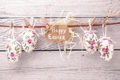 Easter eggs on a string. With flowers on a light wooden background with a congratulatory card ,concept holidays Royalty Free Stock Photo