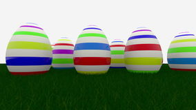 Easter eggs with stripes on green grass. In backgrounds stock video