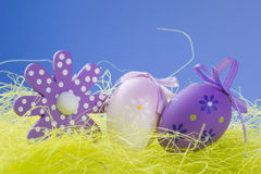 Easter eggs and symbol on grass. With blue background Royalty Free Stock Images
