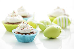 Easter eggs and tasty cupcakes Stock Image
