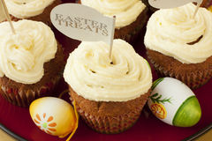 Easter eggs and tasty cupcakes with cream Stock Image