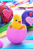 Easter eggs. A teddy chick emerging from a hatched pink egg and some easter eggs painted in different colors and patterns Stock Photos