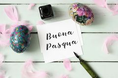 Easter eggs and text happy easter in italian. A piece of paper with the text buona pasqua, happy easter written in italian, an ink bottle, a dip pen, some Stock Photo