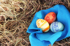 Easter eggs and textile on hay Royalty Free Stock Images