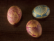 Easter eggs. Three painted Easter eggs on a dark wood texture background.. Decorative hand painted Easter eggs decorated using traditional method with a wax stock images