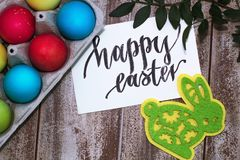 Easter eggs in a tray and jars of paints on a wooden background, three chicken eggs in beautiful female hands, the inscription of. Multi-colored easter eggs in a Royalty Free Stock Photography