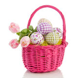 Easter eggs and tulips. Cheerful easter eggs and tulips in a pink wicker basket isolated over white background Royalty Free Stock Photos