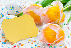 Easter eggs, tulips and blank greeting card on white wooden tabl Royalty Free Stock Photography