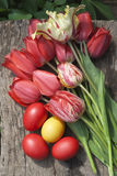 Easter eggs with tulips bouquet. On wood Stock Images