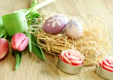 Easter eggs, tulips and candles on wooden Stock Photography