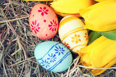 Easter eggs and tulips on hay Stock Images