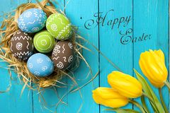 Easter card with colorful eggs in nest and yellow tulips over blue background. Top view with copy space stock photo