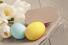 Easter eggs with tulips on table Stock Photography