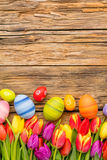 Easter eggs and tulips on wooden background Royalty Free Stock Photography