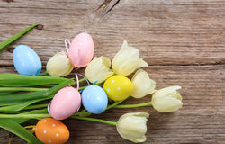 Easter eggs and tulips on wooden background and copy space Stock Image