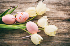 Easter eggs and tulips on wooden background and copy space Royalty Free Stock Photography