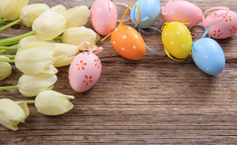 Easter eggs and tulips on wooden background and copy space Royalty Free Stock Photo