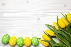 Easter eggs and tulips on wooden background. Stock Photo