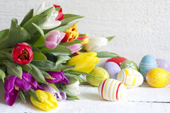 Easter eggs and tulips on wooden board Royalty Free Stock Images