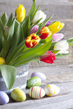 Easter eggs and tulips on wooden board Stock Photos