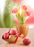Easter eggs and tulips on wooden table on abstract spring backgr Stock Photos