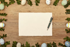 Easter eggs and twigs, blank card and ballpen on wood Stock Images