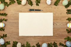Easter eggs and twigs, blank card and ballpen on wood Royalty Free Stock Photos
