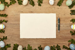 Easter eggs and twigs, blank card and ballpen on wood Royalty Free Stock Photo