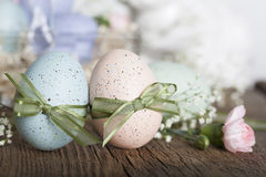Easter Eggs. Two speckled Easter eggs leaning into one another both tied with green ribbon bows and a pink carnation bud at their side Stock Photos