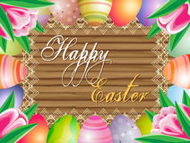 Easter eggs and tylips on the wooden background. Royalty Free Stock Photo