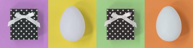 Easter Eggs und Geschenkboxen auf einer mehrfarbigen Fahne mit Quadraten stockbilder