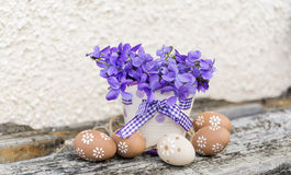 Easter eggs  and vase with purple  violets Stock Images