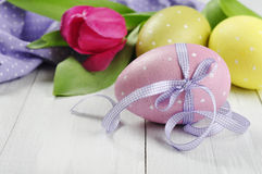 Easter eggs with violet ribbon Stock Photos