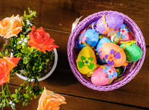 Easter eggs in violett basket and rose flowers in a pot. Top view. Stock Photo