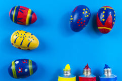 Easter eggs and water colors. On blue background Stock Image