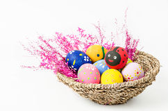 Easter eggs in weave basket with pink flower. Royalty Free Stock Image