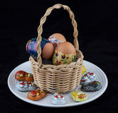 Easter eggs in whicker basket on white plate Royalty Free Stock Images