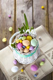 Easter eggs in the white basket on rustic wooden background Royalty Free Stock Photography