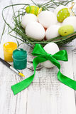 Easter eggs. White easter egg with green ribbon and paints on wooden table stock photo